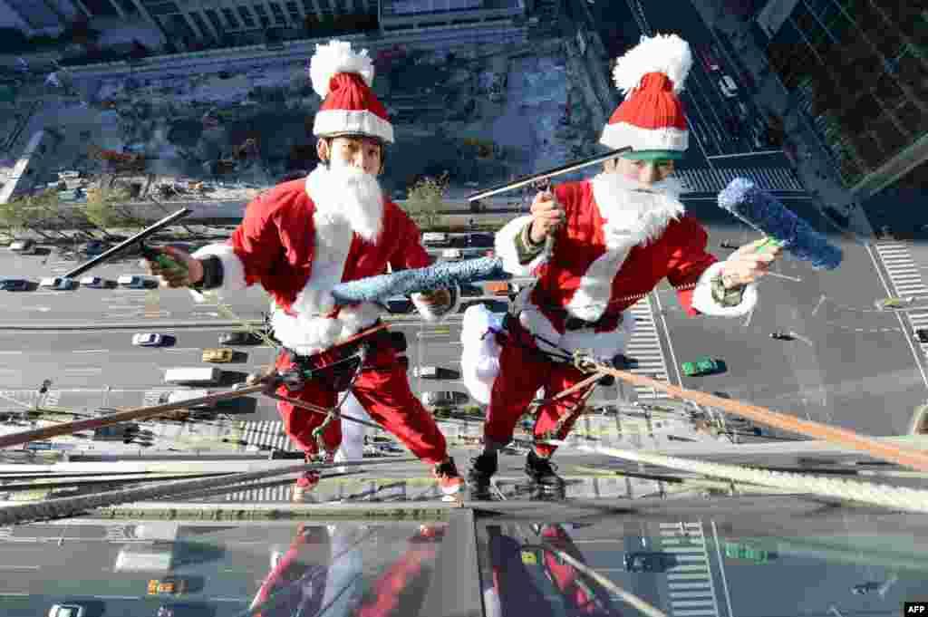 Veshur në kostume babadimri, punëtorët pastrojnë dritaret rreth 55 metra lartësi mbi tokë, jashtë një hoteli në Tokio.