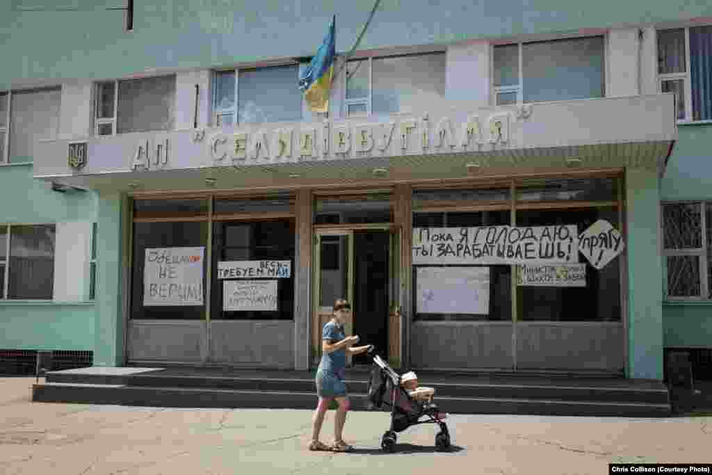 Signs on a mine administration building criticize the Ukrainian government for failing to pay salaries to coal miners.