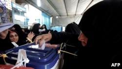 Женщина голосует на выборах президента в Иране