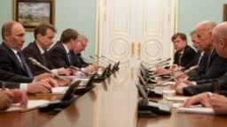 """Then-U.S. Vice President Joe Biden (right) meets with then-Russian Prime Minister Vladimir Putin (left) in Moscow on March 10, 2011. Michael McFaul, the architect of President Barack Obama's Russia """"reset,"""" can be seen at the right rear."""