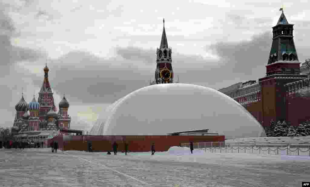 People stand near a huge temporary dome covering the mausoleum of Soviet state founder Vladimir Lenin on Red Square in Moscow. The dome keeps temperatures inside warmer and allows repair works on the mausoleum to continue to meet an end-of-April deadline. (AFP/Alexander Nemenov)