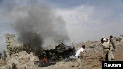 Бойцы гражданской обороны гасят огонь, охвативший военный грузовик на базе, контролируемой повстанцами группировки «Ахрар аль-Шам». Активисты говорят, что это было последствие бомбежки российскими самолетами близ сирийского города Идлиб. 1 октября 2015 года.