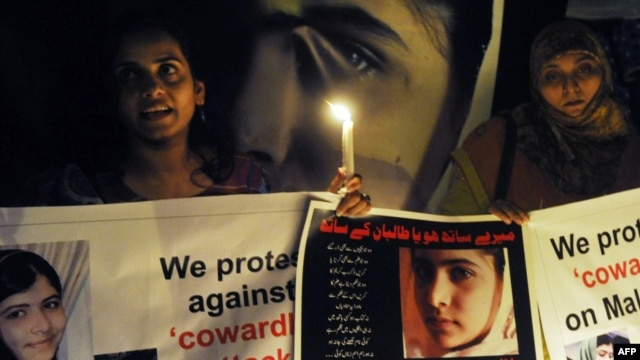 Pakistani civil society activists carry candles to pay tribute to Malala Yousafzai in Lahore.