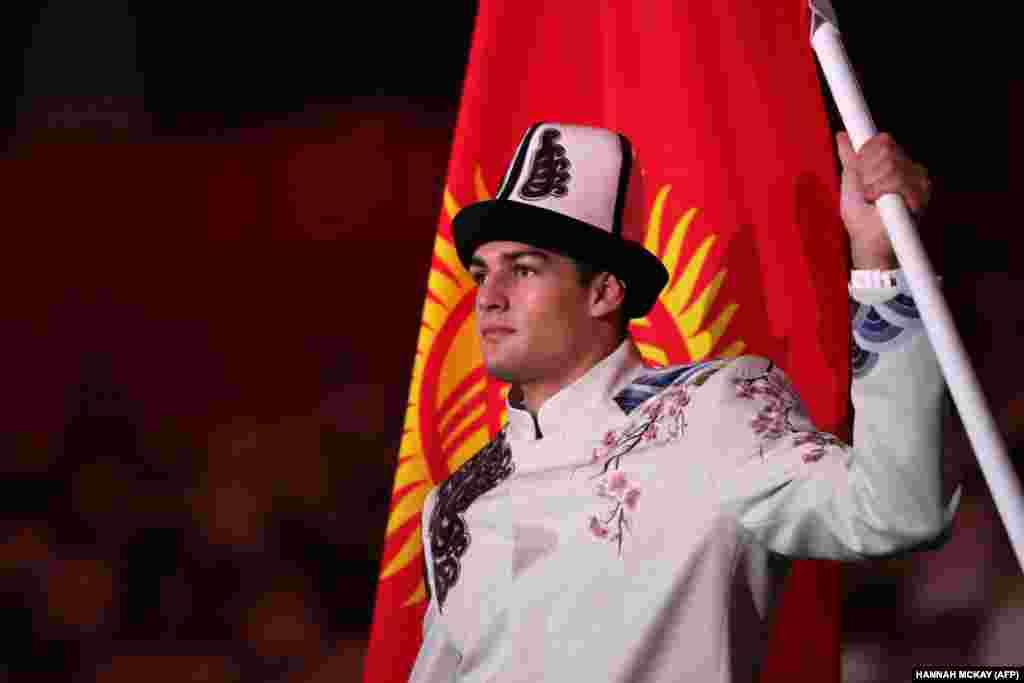 Кыргызстан курама командасынын мүчөсү, суучул Денис Петрашов олимпиаданын ачылуу аземинде Кыргызстандын желегин көтөрүп бара жатат.