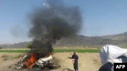 A car is seen on fire at the site of a drone strike believed to have killed Afghan Taliban leader Mullah Akthar Mansur in southwest Pakistan, May 21.