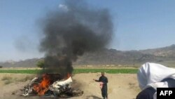 A taxi is seen on fire at the site of a drone strike believed to have killed Afghan Taliban leader Mullah Akthar Mansur in southwest Pakistan on May 21.