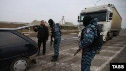 Miliții pro-ruse la punctul de control Cingar pe o șosea spre Crimea, 9 martie 2014.