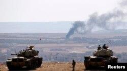 Турецькі танкісти на кордоні з Сирією стежать за повітряними ударами по ісламістах у Кобане на сирійському боці, але в події не втручаються, 8 жовтня 2014 року