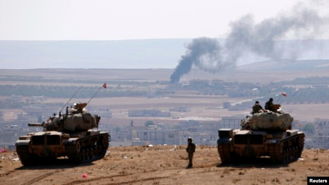 Turkish tanks near the Syrian border look on as smoke rises from the besieged city of Kobani on October 8.