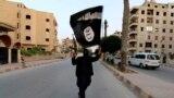 أحد مسلّحي داعش يرفع راية التنطيم الذي سيطر على أجزاء في العراق وسوريا - الرقة 29 حزيران 2014