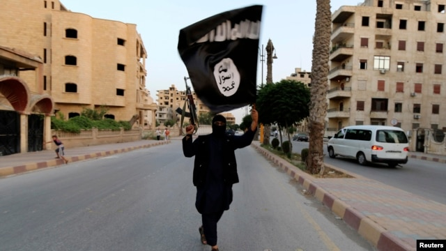 A member loyal to the Islamic State in Iraq and the Levant (ISIL) waves an ISIL flag in Raqqa, Iraq.