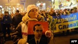 Женщина держит портрет Степана Бандеры во время марша в Киеве. 1 января 2014 года.
