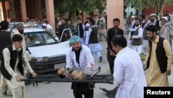Rescue workers carry a child who was injured after an earthquake in Jalalabad on October 26.