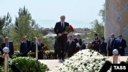 Президент России Владимир Путин (в центре) во время возложения цветов к могиле президента Узбекистана Ислама Каримова на кладбище в Самарканде.