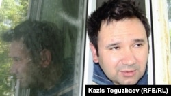 Opposition activist Ainur Qurmanov talks to reporters through the window of his hospital room in Almaty on May 2.