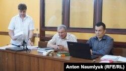 Журналіст Микола Семена (в центрі) та адвокати Олександр Попков (зліва) та Еміль Курбедінов (праворуч) у суді