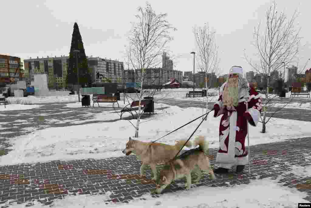 A man dressed as Father Frost walks with Siberian Huskies in a park during an annual Christmas Fair in Krasnoyarsk, Siberia. (Reuters/Ilya Naymushin)