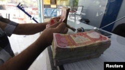 Iraq -- A customer counts Iraqi dinars at a money changer in Baghdad, 01Oct2012