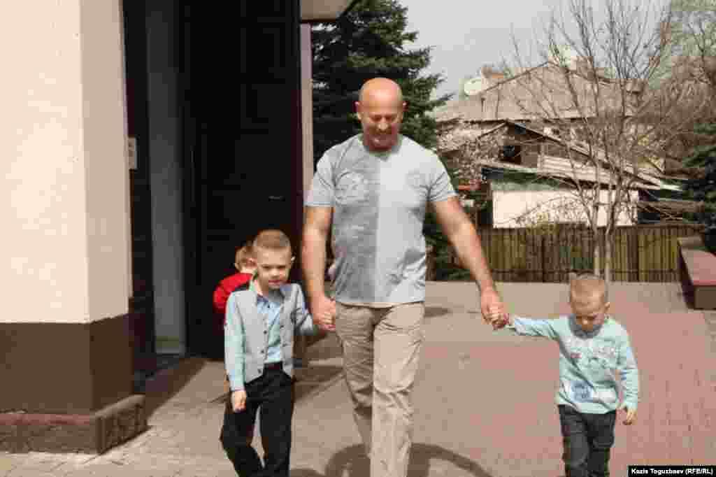 Отец с двумя сыновьями выходит из католического храма после утренней воскресной пасхальной мессы. Алматы, 31 марта 2013 года.