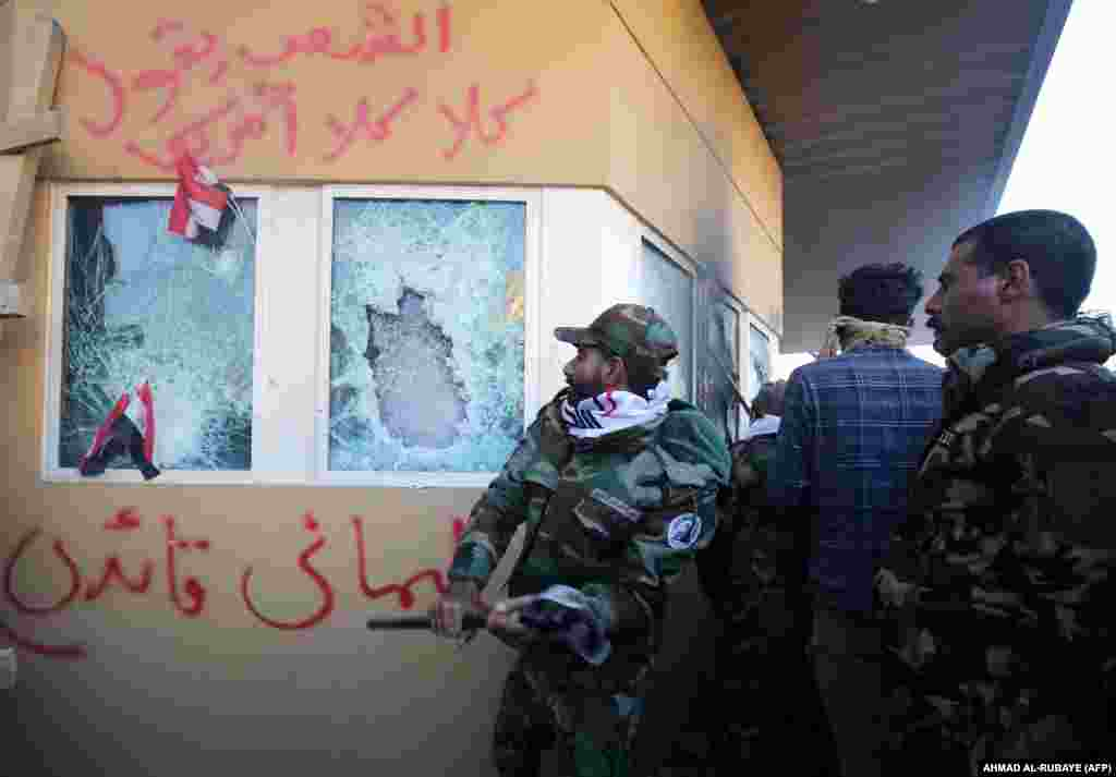 "Members of an Iran-backed Shi'ite militia smash the bulletproof glass of the U.S. Embassy in Baghdad on December 31, 2019. The U.S. military said that Soleimani ""approved the attack"" and had organized several other attacks on U.S.-led coalition bases in Iraq over the past several months."