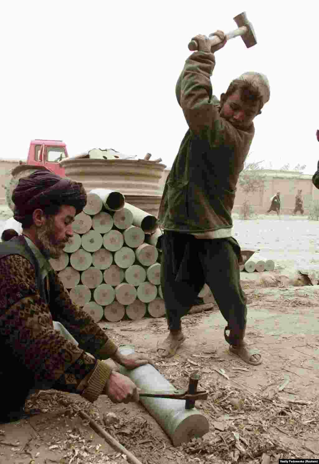 Bărbațidin nordul Afganistanului topesc vechile tuburi de obuzși le transformă în obiecte pentru casă. Deși războiul a încetat în cea mai mare parte a țării după ce talibanii au preluat controlul, aplicarea rigidă a legii islamice și a tradițiilor tribale a cauzat suferințe multor afgani obișnuiți.
