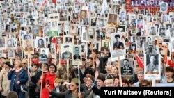 Люди несут портреты людей, в том числе солдати Красной Армии, когда они принимают участие в марше Бессмертного полка на параде Победы, посвященном годовщине победы над нацистской Германией во Второй мировой войне, во Владивостоке, Россия, 9 мая.