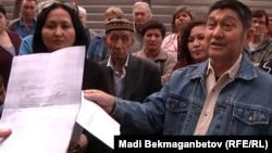 Житель микрорайона Аксай-4 показывает журналистам письмо официального ведомства. Алматы, 7 апреля 2012 года.