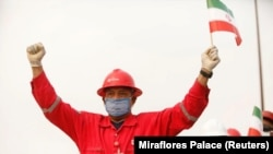 A worker of the Venezuelan state oil company waves an Iranian flag during the arrival of the Iranian tanker ship Fortune at El Palito refinery in Puerto Cabello on May 25.