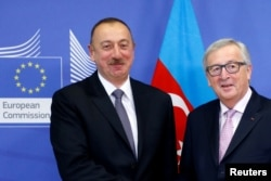Azerbaijani President Ilham Aliyev (left) poses with European Commission President Jean-Claude Juncker ahead of a meeting at the EU Commission headquarters in Brussels on February 6.