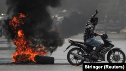 Un protestatar ridică trei degete în semn de salut în timp ce trece pe lângă un morman de cauciucuri în flăcări în timpul protestelor împotriva loviturii de stat, 1 aprilie 2021.