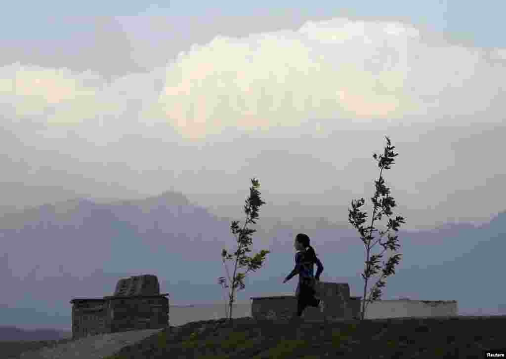 An Afghan girl runs along a path as the sun sets in Kabul. (Reuters/​Mohammad Ismail)