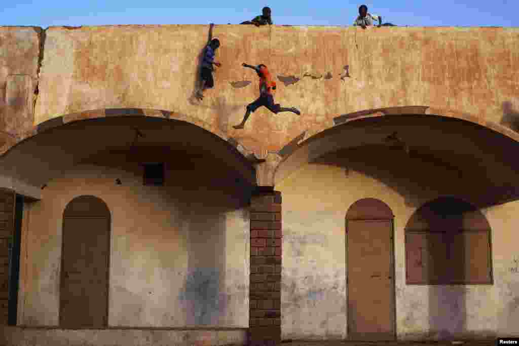Boys play on the roof of the entrance to a football stadium in Gao, Mali. (Reuters/Joe Penney)