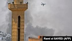 Самолет предположительно сирийских ВВС заметен в небе над районом повстанческого анклава Ярмук под Дамаском. 27 апреля 2018 года.