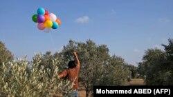 در این عکسی که خبرگزاری فرانسه منتشر کرده فردی در غزه در حال فرستادن بادکنکهای قابل اشتعال به جنوب اسرائیل است
