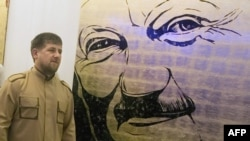 Разман Кадыров на фоне портрета Ахмата Кадырова (архивное фото)