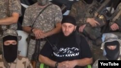 The address to North Caucasus Muslims is delivered by a wheelchair-bound fighter identified as Salakhuddin (center), who appears to have lost both legs.