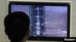 Një shkencëtar shikon në monitor raketën Unha-3 nga baza e lëshimit, Phenian, 11 prill 2012