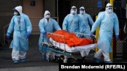 Медицинские работники везут каталку с телом умершего от осложнений, вызванных коронавирусом, Нью-Йорк, Бруклин, 4 апреля 2020 года
