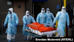 Медики клиники в Нью-Йорке выносят тело человека, умершего от коронавируса.