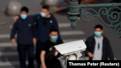 Қытай астанасында адамдар өтіп жатөан көшеде жұмыс істеп тұрған бақылау камерасы.