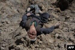 Мальчик, потерявший всю семью, лежит на месте, где погребены его родные