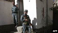 Afghan policemen stand guard near the body of a suicide bomber inside a United Nations compound in Herat.