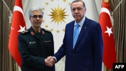 Turkish President Recep Tayyip Erdogan (right) welcomes General Mohammad Hossein Baqeri in Ankara on August 16.