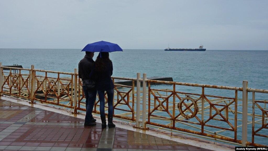 Парочка на набережной и танкер на алуштинском рейде