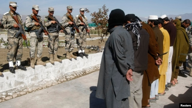 Taliban militants who were arrested by Afghan police stand during a presentation of seized weapons and equipment in Jalalabad on March 2.