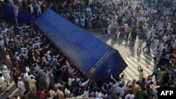 Pakistani demonstrators topple a freight container placed by police to block a street during a protest against an anti-Islam film in Lahore on September 21.