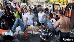 Иерусалимдегі гей-парадта зардап шеккен адамды медициналық жедел жәрдем көлігіне салып жатыр. 30 шілде 2015 жыл.