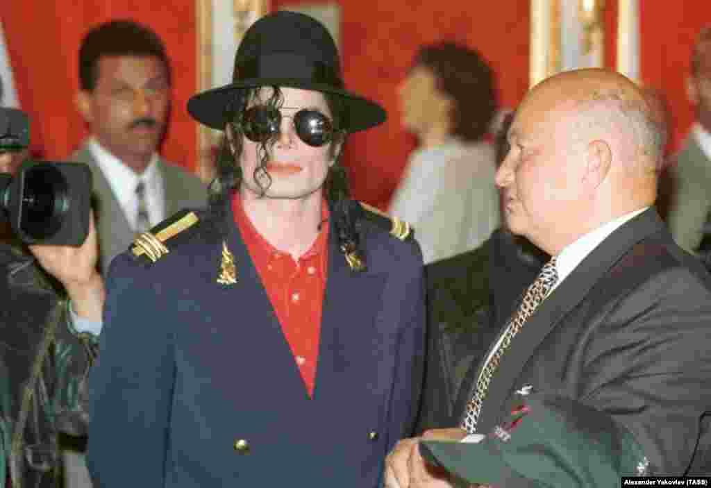 Лужков (праворуч) влаштовує в своєму московському офісі прийом для американської поп-зірки Майкла Джексона. Той був у Москві в рамках свого світового турне HIStory World Tour. 16 вересня 1996 року