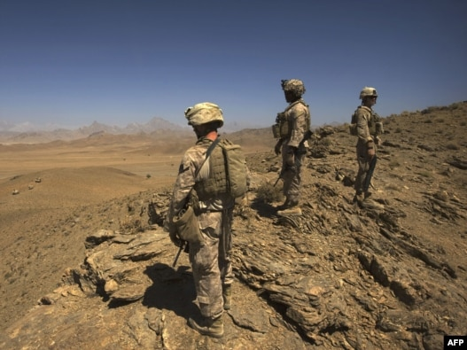 U.S. Marines stand on a hill after clearing through a cave while on patrol in Farah Province, Afghanistan, in 2009.