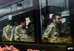 Detained Turkish soldiers who allegedly took part in a military coup arrive in a bus at the courthouse in Istanbul on July 20.
